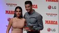 Cristiano Ronaldo bersama kekasihnya Georgina Rodriguez berpose setelah meraih penghargaan MARCA Legend award di Reina Victoria Theater, Madrid (30/7/2019). Di acara tersebut Ronaldo mengaku berharap dapat kembali ke Real Madrid. (AFP Photo/Javier Soriano)