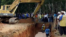 Alat berat disiagakan di sekitar lokasi pemakaman massal jenazah yang di duga etnis Rohingya di Alor Setar, Malaysia, Senin (22/6/2015).  21 dari 106 jenazah tak dikenal yang ditemukan bulan lalu dimakamkan hari ini. (Reuters/Olivia Harris)