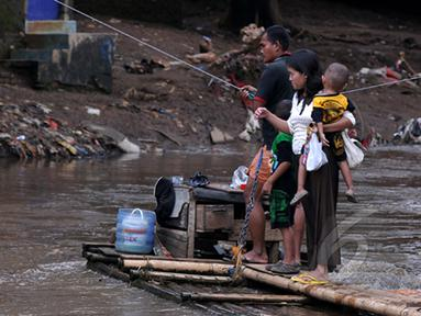 Masih banyak warga bantaran kali Ciliwung Jakarta yang memanfaatkan air kali untuk kehidupan sehari - hari. Tampak aktivitas warga saat menyebrangi kali Ciliwung, Jakarta, Jumat (20/2/2015). (Liputan6.com/JohanTallo)