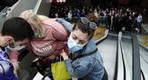 Seorang wanita dibantu naik eskalator saat orang antre vaksinasi dan menjadi salah satu orang yang menerima kupon belanja, di pusat perbelanjaan Usce di Beograd, Kamis (6/5/2021). Pemerintah Serbia menawarkan uang Rp 430 ribu bagi warganya yang divaksinasi sebelum akhir Mei. (AP/Darko Vojinovic)