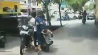 Tiga remaja menaiki sebuah sepeda motor berjenis skuter matik (skutik). Salah satu remaja terlihat menggunakan rok sekolah berwana biru.