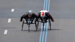 Atlet asal Swiss, Marcel Hug (kiri) dan atlet asal Afrika Selatan, Ernst Van Dyk bersaing dalam kejuaraan balap kursi roda kategori pria pada ajang Boston Marathon ke-121 di Boston, Senin (17/4). (AP Photo/Charles Krupa)