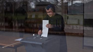 Seorang wanita memasukkan surat suara ke kotak suara saat pemilihan umum Belanda di sebuah sekolah yang dijadikan Tempat Pemungutan Suara (TPS) di Staphorst, Rabu (15/3). Kotak suara yang tersedia terbuat dari tempat sampah. (AP Photo/Muhammed Muheisen)