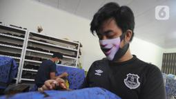 Perajin menyelesaikan proses pembuatan batik di  Batik Tradisiku, Bogor, Jawa Barat, Kamis (6/8/2020). Perajin batik mitra binaan Pertamina ini berinovasi dengan membuat motif dan warna baru untuk mengatasi anjloknya penjualan batik sebagai dampak ekonomi wabah corona. (merdeka.com/Arie Basuki)