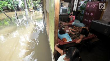 Warga beristirahat di dalam rumah saat banjir menggenangi kawasan Rawa Terate, Cakung Jakarta, Rabu (30/1). Ratusan rumah di RT 016/004 dan RT 010/005 Kelurahan Rawa Terate, terendam banjir sejak dini hari. (merdeka.com/Iqbal S. Nugroho)