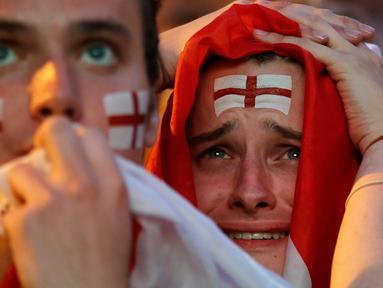 Suporter timnas Inggris bersedih setelah timnya kalah dari Kroasia pada babak semifinal Piala Dunia 2018 saat menonton siaran langsung di Flat Iron Square, London, Rabu (11/7). Langkah Inggris di Piala Dunia 2018 terhenti oleh Kroasia. (AP/Luca Bruno)
