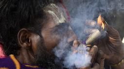 Seorang Sadhu atau orang suci Hindu menghisap ganja menggunakan 'chillum', pipa tanah liat tradisional, menjelang festival Hindu 'Maha Shivaratri', di Kathmandu (9/3/2021). Festival ini juga menandai hari penyempurnaan pernikahan Siwa. (AFP/Prakash Mathema)