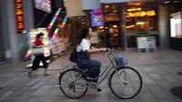 Seorang wanita mengendarai sepedanya di sebuah jalan di Nagoya, Jepang (24/9/2019). Kota Nagoya terletak di Daratan rendah Nōbi, bagian barat daya Prefektur Aichi. (AP Photo/Christophe Ena)