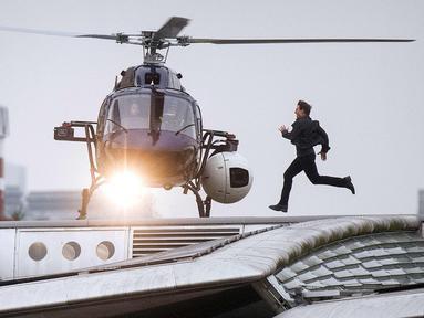 """Aktor Tom Cruise berlari mengejar helikopter dalam adegan syuting film """"Mission: Impossible"""" 6  di sepanjang Jembatan Blackfriars di London, Inggris (14/1). Adegan Tom Cruise ini membuat kegemparan warga sekitar. (Victoria Jones / PA via AP)"""
