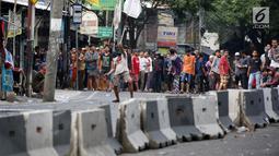 Massa bertopeng menantang aparat keamanan saat terjadi bentrok di kawasan Slipi, Jakarta Barat, Rabu (22/5/2019). Polisi membalas lemparan batu para pengunjuk rasa dengan menembakkan gas air mata. (Liputan6.com/Gempur Muhammad Surya)