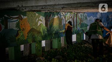 Mahasiswa Institut Kesenian Jakarta (IKJ) menyelesaikan pembuatan mural di kolong Jembatan Pegangsaan, Menteng, Jakarta, Selasa (26/1/2021). Pembuatan mural tersebut merupakan bagian dari pembangunan taman kolong jembatan oleh Pemprov DKI Jakarta. (Liputan6.com/Faizal Fanani)