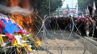 Karangan bunga untuk Ahok-Djarot dibakar oleh orang yang diduga menjadi provokasi saat aksi Hari Buruh di Jalan Medan Merdeka Barat, Jakarta, Senin (1/5). (Liputan6.com/Yoppy Renato)