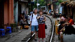 Foto pada 8 Juni 2019 memperlihatkan wisatawan berswafoto di tengah jalur kereta api populer di Hanoi. Di ibu kota Vietnam tersebut rel-rel kereta yang berada di permukiman padat penduduk dijadikan destinasi wisata selfie. (Photo by Manan VATSYAYANA / AFP)