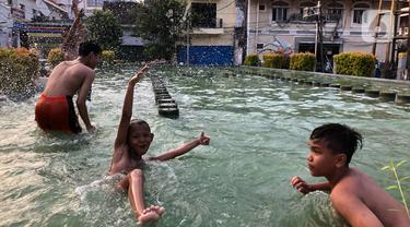 Anak-anak berenang di kolam penghias taman Pasar Baru di Jakarta, Rabu (2/9/2020). Meskipun terdapat larangan, namun sejumlah anak tetap nekat berenang di kolam tersebut sehingga mengganggu ketertiban umum. (Liputan6.com/Immanuel Antonius)