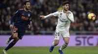 Gelandang Real Madrid, Marco Asensio, berebut bola dengan gelandang Valencia, Daniel Parejo, pada laga La Liga di Stadion Santiago Bernabeu, Madrid, Sabtu (1/12). Madrid menang 2-0 atas Valencia. (AFP/Oscar Del Pozo)