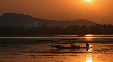Seorang nelayan Kashmir mengayuh perahunya saat matahari terbenam di danau Dal di Srinagar, India (12/9). Danau Dal dijuluki sebagai Jewel in the Crown of Kashmir atau Srinagar Jewel. (AFP Photo/Tauseef Mustafa)
