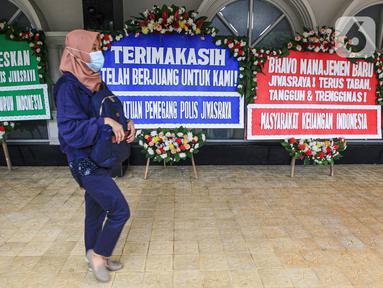 Seorang wanita berjalan dekat karangan bunga di halaman Kantor PT Asuransi Jiwasraya (Persero), Jakarta, Selasa (15/12/2020). Nasabah Jiwasraya ramai-ramai mengirimkan karangan bunga ke Kantor PT Asuransi Jiwasraya (Persero). (Liputan6.com/Faizal Fanani)