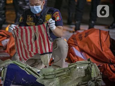 Petugas kepolisian memeriksa pakaian korban kecelakaan pesawat Sriwijaya Air nomor penerbangan SJ 182 rute Jakarta-Pontianak pada hari ketujuh operasi SAR pesawat tersebut di JICT II Tanjung Priok, Jakarta Utara, Jumat (15/1/2021). (Liputan6.com/Faizal Fanani)