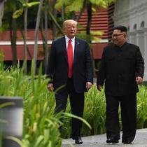 Suasana saat Presiden AS Donald Trump (kiri) dengan Pemimpin Korea Utara Kim Jong-un berjalan di taman Hotel Capella, Pulau Sentosa, Singapura, Selasa (12/6). Trump dan Kim optimis bahwa KTT akan sukses. (Anthony Wallace/Pool/AFP)