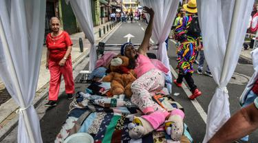 Seorang wanita Kolombia berbaring di tempat tidur saat ambil bagian dalam pawai merayakan Hari Kemalasan Sedunia di Itagui, dekat Medellin, Minggu (19/8). Upaya unik itu untuk medesak para perkerja yang tertekan agar bersantai. (AFP/JOAQUIN SARMIENTO)