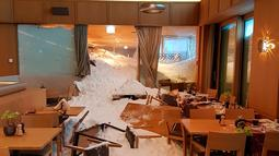Petugas membersihkan longsoran salju yang masuk ke dalam Hotel Saentis di Schwaegalp, Swiss, Jumat (11/1). Badai salju tengah melanda Swiss dan sejumlah negara di Eropa. (Gian Ehrenzeller/Keystone via AP)