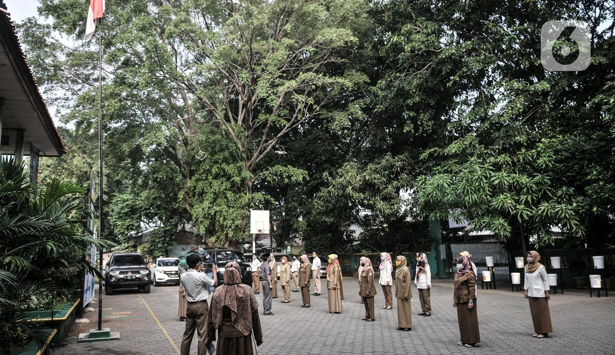 Para guru mengikuti upacara sebelum memulai Masa Pengenalan Lingkungan Sekolah (MPLS) siswa Tahun Ajaran Baru 2020/2021 secara daring atau online di SDN Pekayon Jaya 6, Bekasi, Jawa Barat, Senin (13/7/2020). (merdeka.com/Iqbal S. Nugroho)