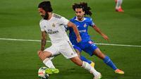 Gelandang Real Madrid, Isco, berebut bola dengan bek Getafe, Marc Cucurella, pada laga lanjutan La Liga pekan ke-33 di Stadion Alfredo Di Stefano, Jumat (3/7/2020) dini hari WIB. Real Madrid menang 1-0 atas Getafe. (AFP/Gabriel Bouys)