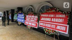 Sejumlah tentara melihat karangan bunga di halaman Kantor PT Asuransi Jiwasraya (Persero), Jakarta, Selasa (15/12/2020). Nasabah Jiwasraya ramai-ramai mengirimkan karangan bunga ke Kantor PT Asuransi Jiwasraya (Persero). (Liputan6.com/Faizal Fanani)