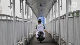 Pengendara sepeda motor melintasi JPO di Jalan Yos Sudarso, Jakarta, Senin (12/11). Aksi nekat yang dilakukan para pengendara sepeda motor demi mempersingkat rute jalan tersebut dapat membahayakan diri mereka sendiri. (Merdeka.com/Iqbal S. Nugroho)