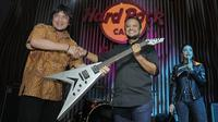 CEO Rajawali Indonesia Communication, Anas Syahrul Alimi (kanan) menyerahkan gitar bertanda tangan personel Megadeth kepada pemenang lelang, yang diwakil Edy Gun, di Hard Rock Cafe, Jakarta, Jumat (30/11). (New Fimela/Bambang Eros)