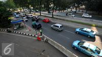 Petugas mengatur kendaraan yang melintas di Jalan Jenderal Sudirman, Semanggi, Jakarta, Rabu (8/6/2016). Jalur cepat dari arah Sudirman menuju Cawang ditutup sementara terkait pengerjaan proyek pembangunan jembatan layang. (Liputan6.com/Yoppy Renato)