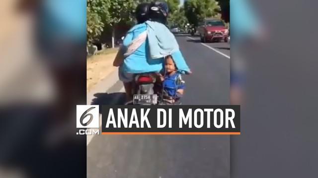 Seorang ibu yang sedang dibonceng motor nekat menaruh anaknya di keranjang. Mirisnya, keranjang tersebut berada tepat di atas knalpot. Pemandangan tak lazim ini berhasil direkam oleh pengendara lainnya.