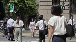 Orang-orang yang memakai masker melintasi persimpangan di Tokyo Kamis (5/8/2021). Meningkatnya kasus virus corona di sejumlah wilayah di Jepang, termasuk Tokyo, membuat pemerintah memperluas status darurat terbatas Covid-19 ke delapan prefektur. (AP Photo/Kantaro Komiya)
