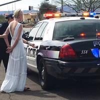 Dalam foto yang viral tersebut terlihat pengantin wanita dimasukkan ke dalam mobil polisi dengan tangan diborgol. (Foto: Marana Police Department via AP, file)