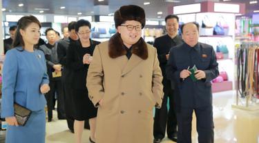 Pemimpin Korea Utara, Kim Jong-un berjalan sambil tersenyum mengunakan jaket dan topi tebal saat mengunjungi pusat perbelanjaan Mirae Shop yang baru dibangun di kompleks Mirae Shop di Korea Utara (28/3). (REUTERS/KCNA)