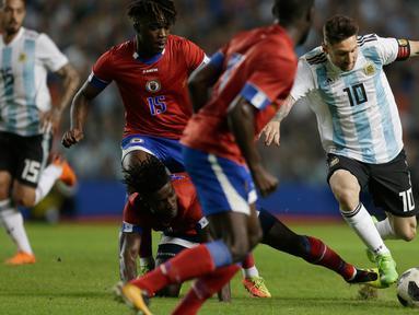 Penyerang Argentina Lionel Messi menggiring bola melewati pemain Haiti saat pertandingan persahabatan di stadion Bombonera di Buenos Aires (29/5). Argentina menang telak 4-0 atas Haiti. (AP / Natacha Pisarenko)