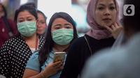 Calon penumpang kereta api mengenakan masker saat berada di Stasiun Gambir, Jakarta Pusat, Jumat (31/01). Dalam rangka pencegahan Virus Corona, PT Kereta Api Indonesia (persero) melakukan sosialisasi kepada penumpang dengan membagi-bagikan masker di stasiun Gambir. (merdeka.com/Imam Buhori)