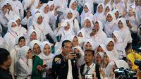 Presiden Joko Widodo atau Jokowi berswafoto dengan siswa SMA penerima Kartu Indonesia Pintar (KIP) di Gorontalo, Jumat (1/3). Tahun 2019 Provinsi Gorontalo mendapatkan jatah 80.502 KIP. (Liputan6.com/Arfandi Ibrahim)