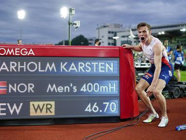 Pelari Norwegia Karsten Warholm melakukan selebrasi di depan papan skor usai memenangkan ajang Diamond League di Oslo, Norwegia, Kamis (1/7/2021). Karsten Warholm memecahkan rekor dunia lari gawang 400 meter putra dengan torehan waktu 46,70 detik. (Fredrik Hagen, NTB via AP)