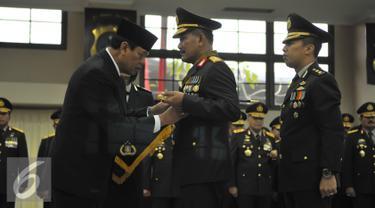 Menkopolhukam, Tedjo Edy Purdjianto (kiri) menyematkan tanda kehormatan Bintang Bhayangkara Utama ke Kapolri Jenderal Badrodin Haiti (tengah)di Jakarta, Senin (29/6/2015). (Liputan6.com/Herman Zakharia)