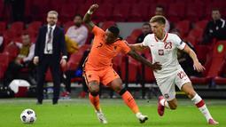 Penyerang Belanda, Steven Bergwijn, berebut bola dengan penyerang Polandia, Krzysztof Piatek, pada laga UEFA Nations League di Stadion Johan Cruijff Arena, Amsterdam, Sabtu (5/9/2020) dini hari WIB. Belandang menang 1-0 atas Polandia. (AFP/John Thys)