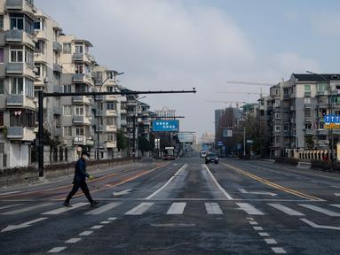 Pria bermasker menyeberangi jalanan yang sepi dekat kantor pusat Alibaba di Kota Hangzhou, Provinsi Zhejiang, China, Rabu (5/2/2020). Pemerintah Hangzhou memberlakukan pembatasan pergerakan bagi warganya menyusul mewabahnya virus corona. (NOEL CELIS/AFP)
