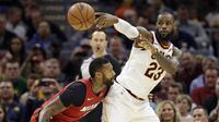 Pemain Cleveland Cavaliers, LeBron James (23) memberikan umpan melewati adangan pemain Miami Heat, James Johnson (16) pada lanjutan NBA basketball game, di Quicken Loans Arena, Cleveland, (28/11/2017). Cavs menang 108-97. (AP/Tony Dejak)