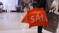 Pembeli membawa belanjaan saat midnight sale di gerai Debenhams, Senayan City, Jakarta, Sabtu (30/12). Tutupnya gerai Debenhams karena perubahan gaya berbelanja masyarakat. (Liputan6.com/Fery Pradolo)