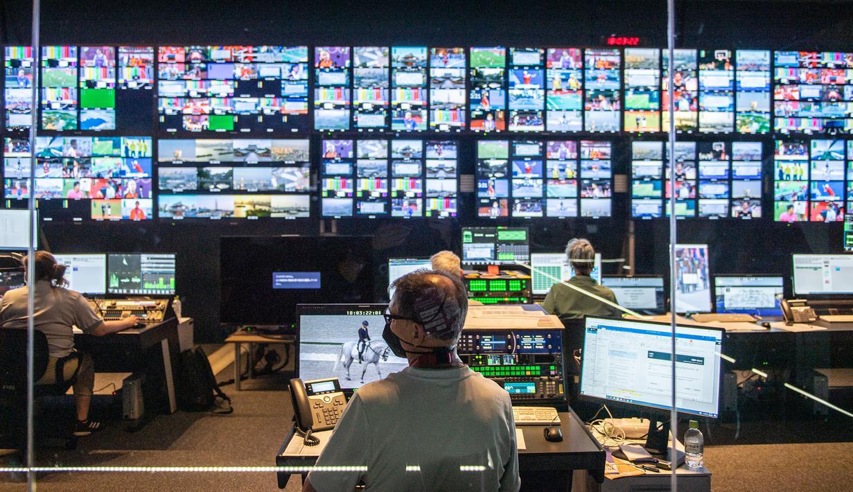 Seorang anggota staf (tengah) bekerja di pusat pengalihan komentar di Olympic Broadcasting Services (OBS) di International Broadcast Center (IBC) di Tokyo pada 28 Juli 2021, selama Olimpiade Tokyo 2020. (AFP/Philip Fong)