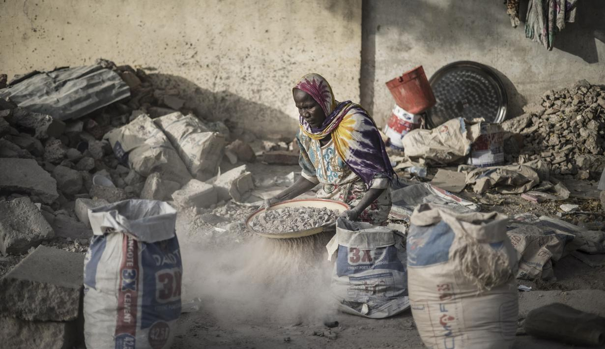 Habiba, penghancur kerikil berusia 50-60 tahun, mengayak dengan saringan improvisasi untuk memisahkan kerikil dari pasir di dekat Cite International des Affaires, N'Djamena, Chad, 12 April 2021. Dalam debu dan panas, wanita Chad menghancurkan kerikil untuk memenuhi kebutuhan. (MARCO LONGARI/AFP)
