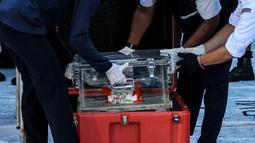 Petugas KNKT meletakkan Black box pesawat Sriwijaya Air SJ 182 yang jatuh di Kepulauan Seribu di Dermaga JICT, Jakarta, Selasa (12/1/2021). Black box yang terdiri dari dua kombinasi perangkat yaitu CVR atau percakapan dalam kokpit pesawat dan FDR atau rekaman data penerbangan. (Liputan6.com/Johan Ta
