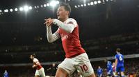Gelandang Arsenal, Mesut Ozil, merayakan gol yang dicetaknya ke gawang Leicester pada laga Premier League Inggris di Stadion Emirates, London, Senin (22/10). Arsenal menang 3-1 atas Leicester. (AFP/Glyn Kirk)