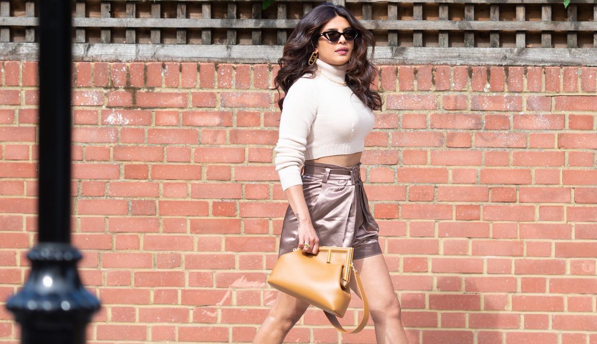 Priyanka Chopra terlihat mengenakan tas FENDI First dengan sweater turtleneck lengan panjang dan rok yang semuanya bernuansa earth tone. Foto: Document/FENDI.