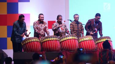 Menko Perekonomian Darmin Nasution (tengah) didampingi  Ketua OJK Wimboh Santoso (kedua kanan) dan Dirut BEI Inarno Djajadi (kiri) memukul gong saat membuka Capital Market Summit & Expo 2019 di Balai Sidang Jakarta Convention Center (JCC), Jakarta, Jumat (23/8/2019). (Liputan6.com/Angga Yuniar)